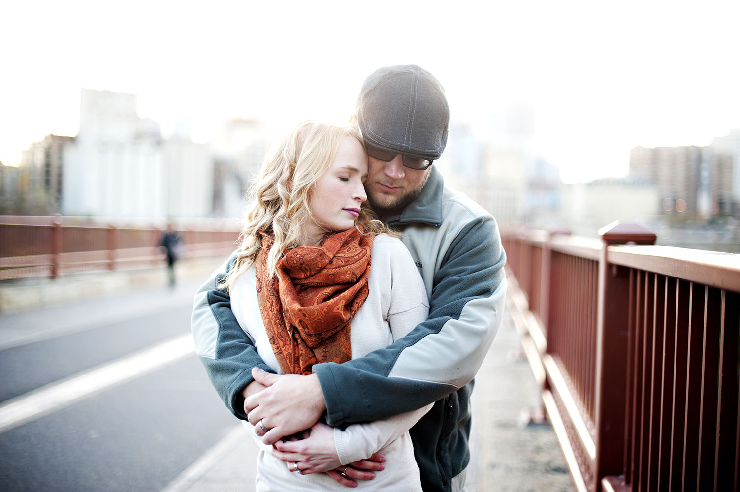 couple embracing on stone arch bridge