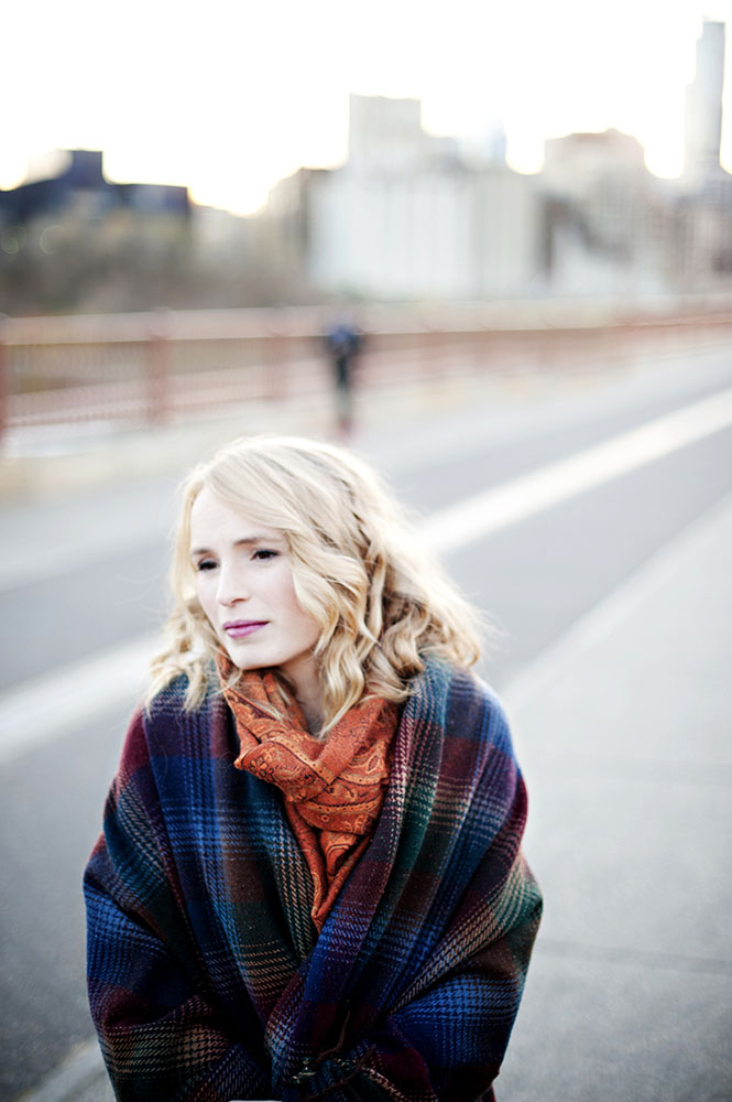 blonde woman with orange scarf and blue and purple blanket