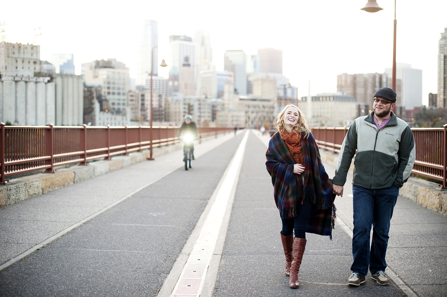 engaged couple walking on the stone arch bridge laughing