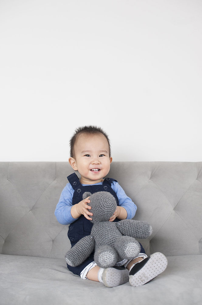 little boy on grey couch in studio with toy