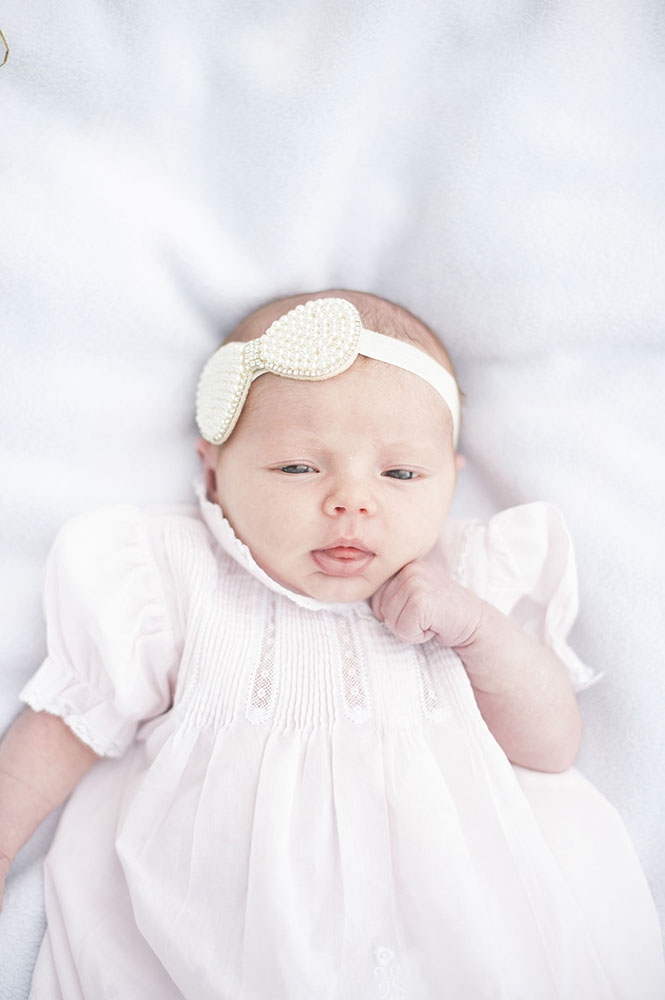 newborn girl with pink dress and bow