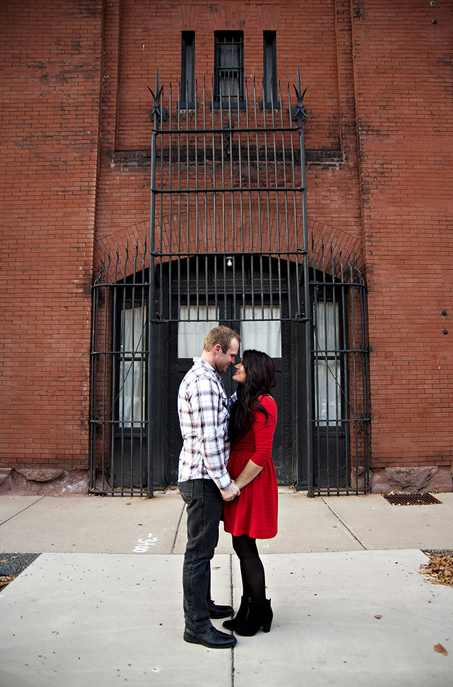 a couple in front of a brick building woman in red dress