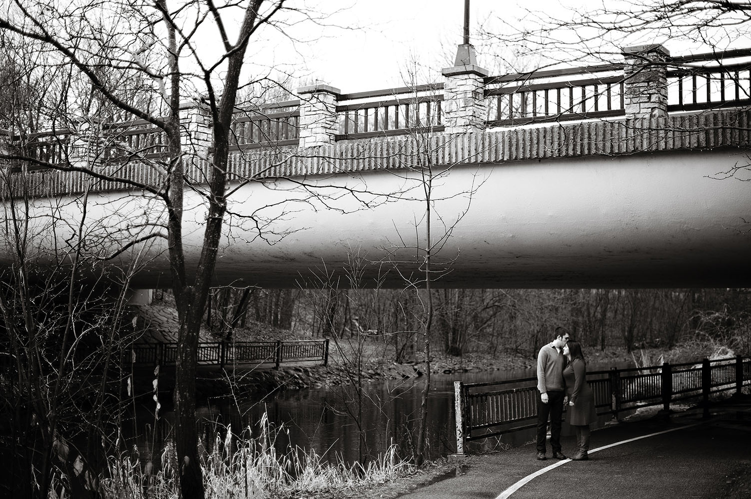 a couple kissing under a bridge
