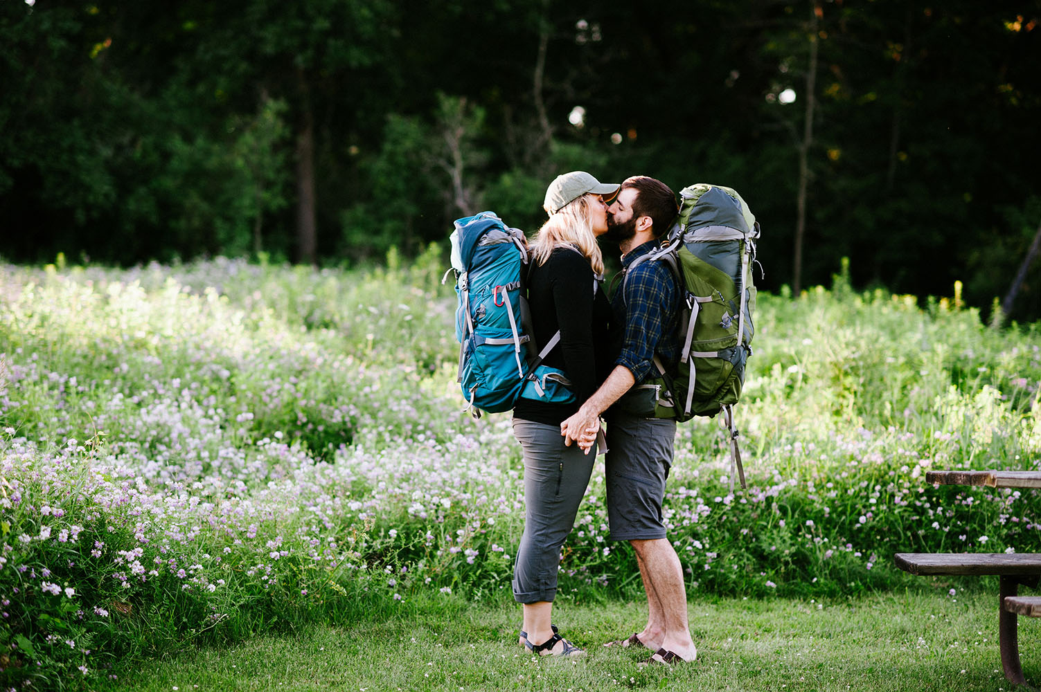 a couple kissing with backpacks