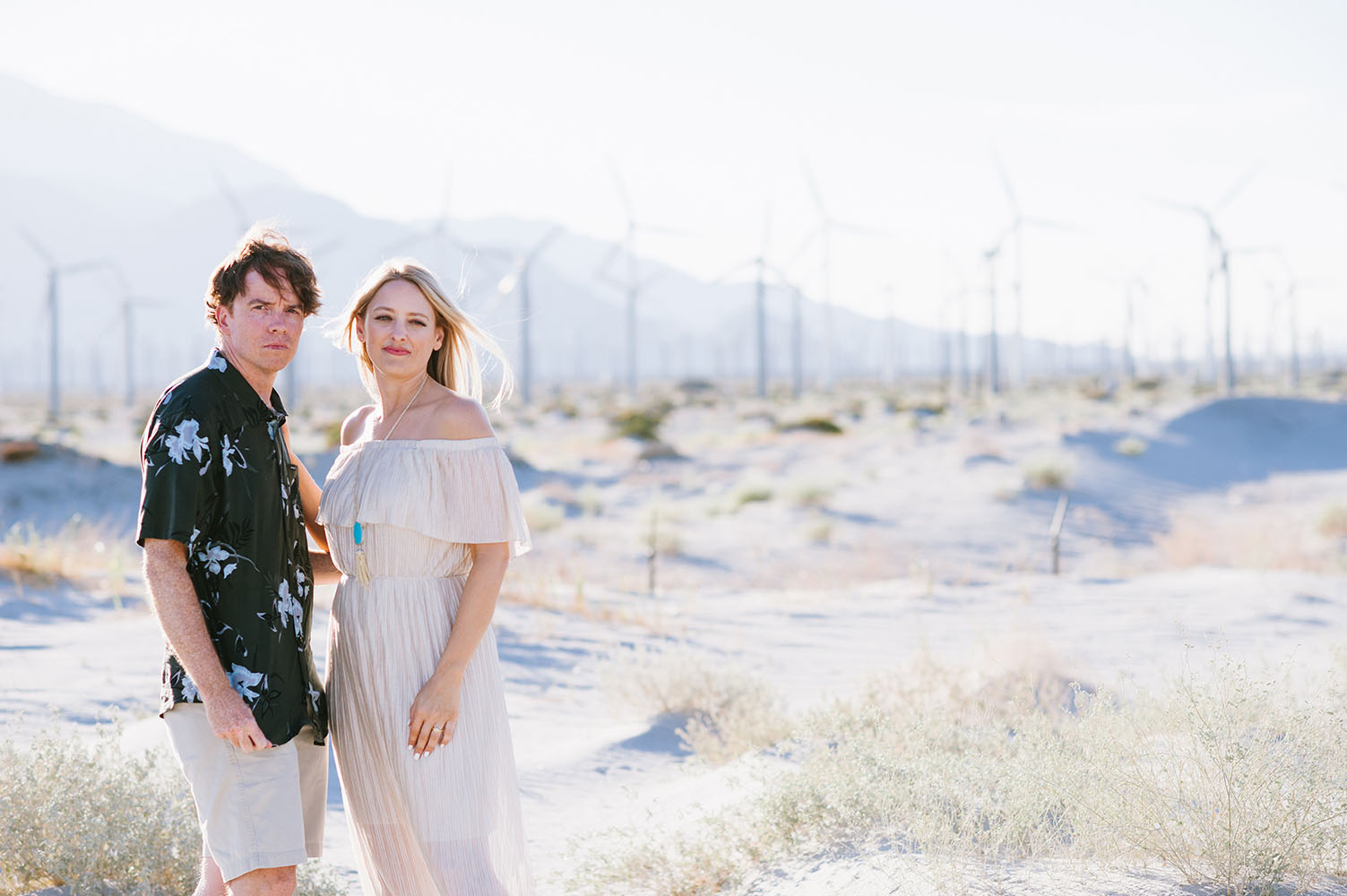 engaged couple in front of wind turbines in California