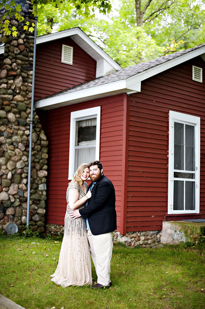 girl in sequin dress guy in suit in front of cabin