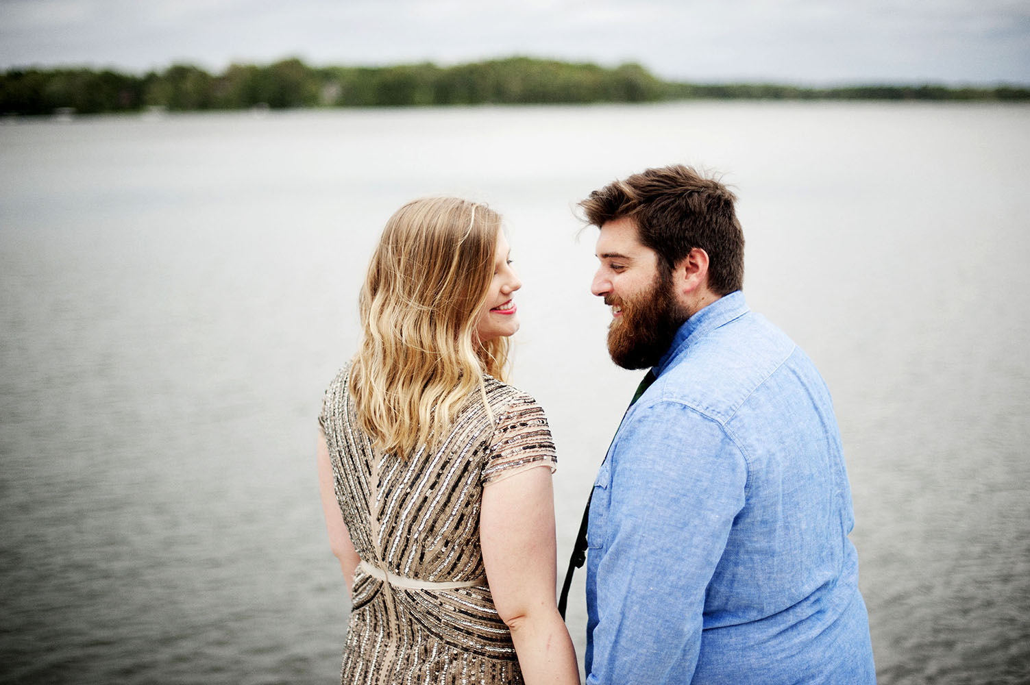 girl in sequin dress and guy in blue shirt by the water
