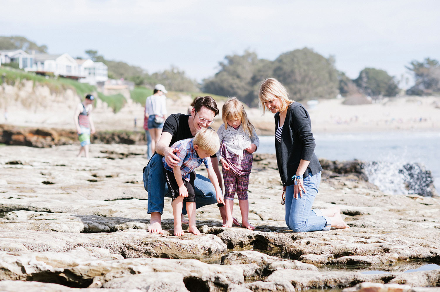 Family looking at tide pools by the ocean