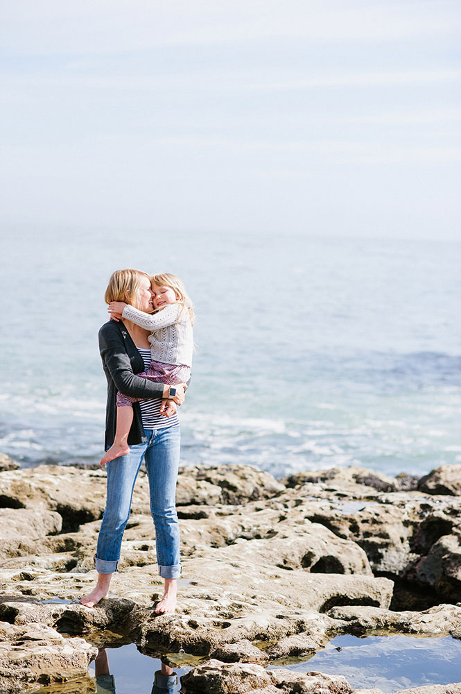 Mom and little girl hugging by the ocean