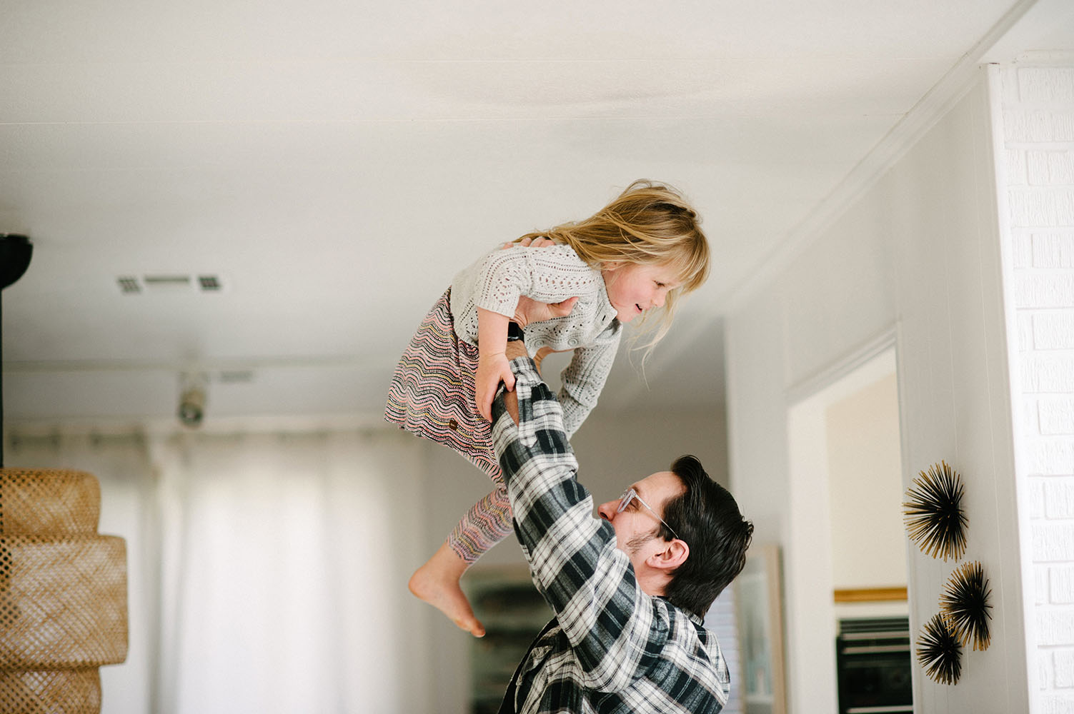 Dad lifting little girl in the air