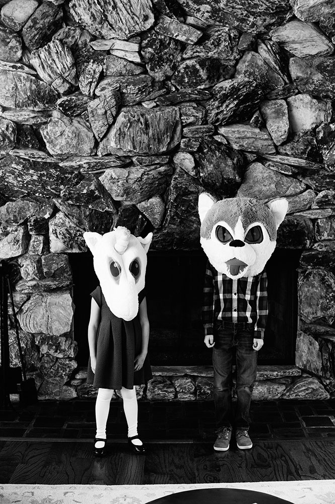 black and white photo of girl and boy with unicorn and wolf heads