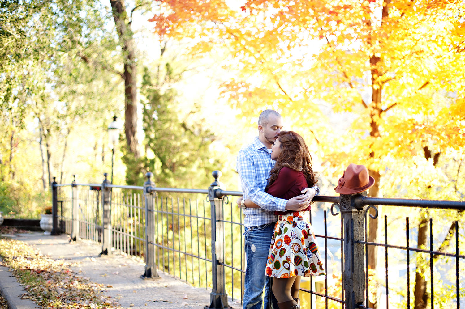 couple embracing in front of a bright fall colored tree