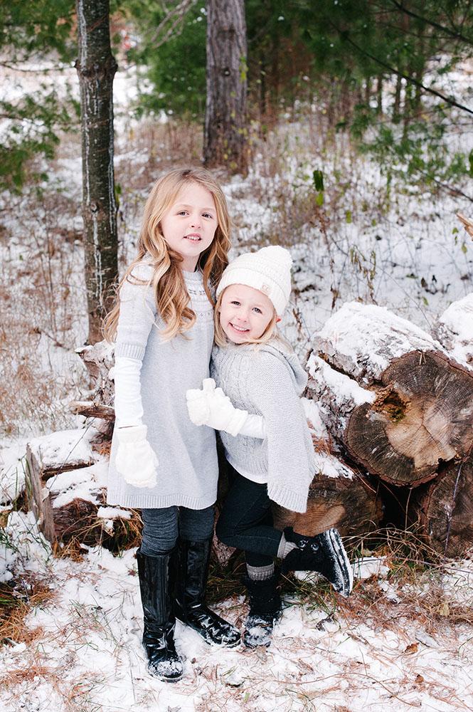 Two little girls in grey outside in the winter