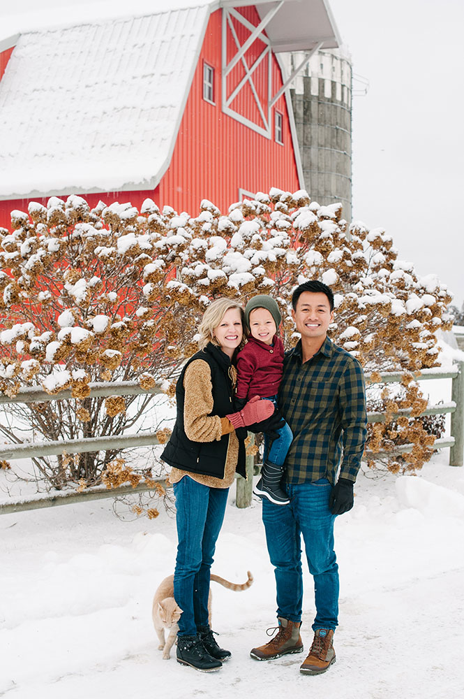 Family in front of a red barn with an orange cat in the winter