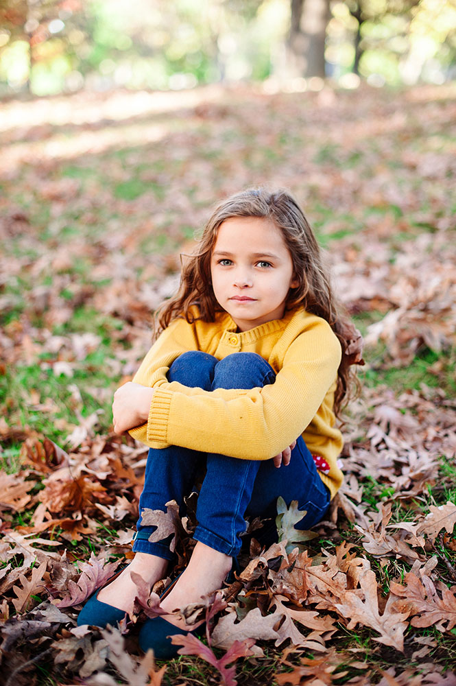 Young girl in yellow sweater and jeans in the leaves
