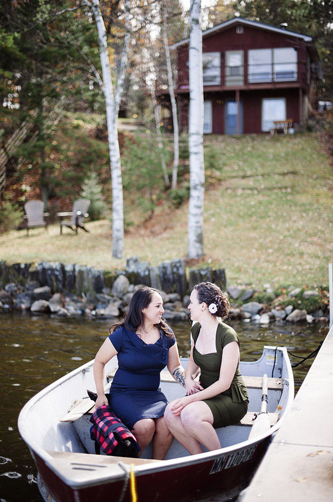 Same sex married women in fishing boat by cabin with dog