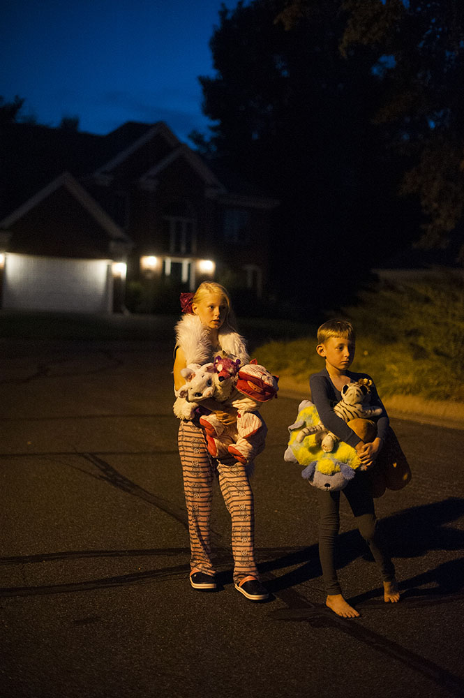 two kids on the street in the dark with stuffed animals