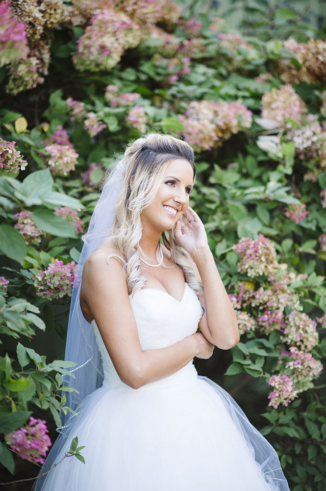 bride in front of hydrangea bush at Camrose HIll