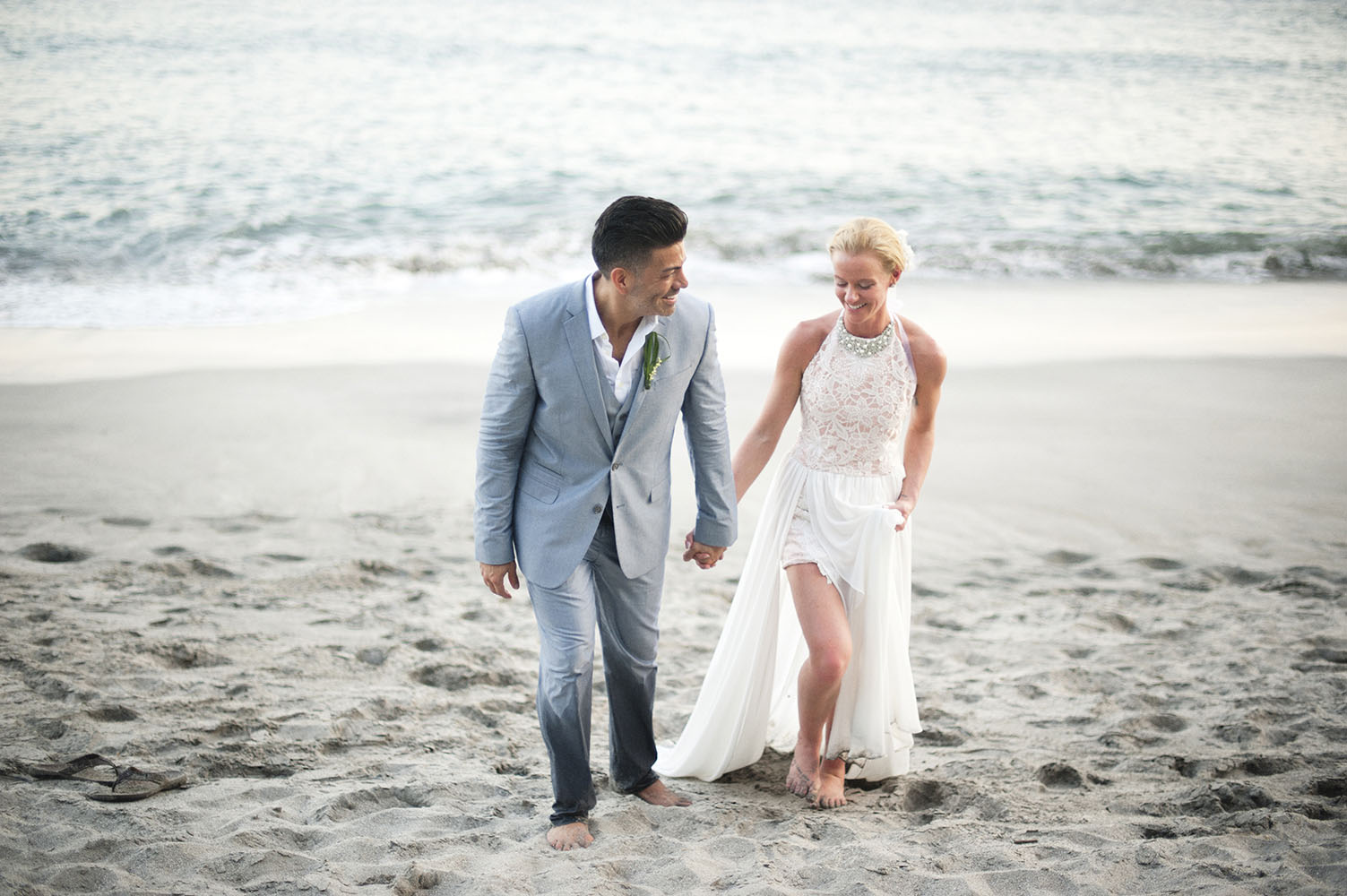 bride and groom walk on beach in Costa Rica