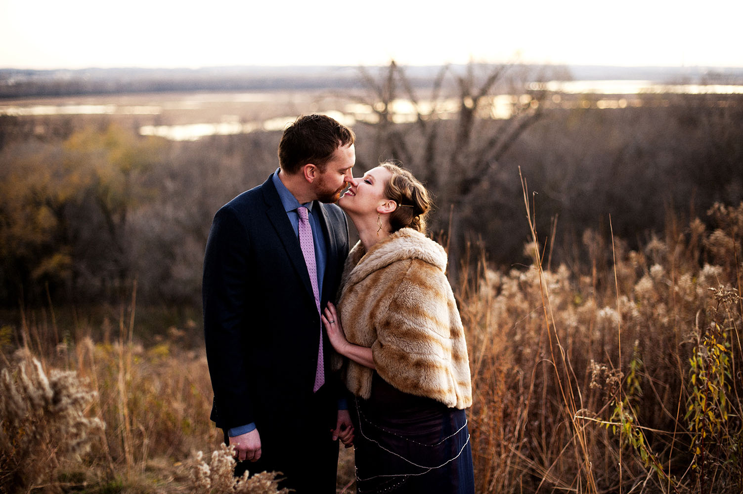married couple kissing overlooking Mississippi River Valley