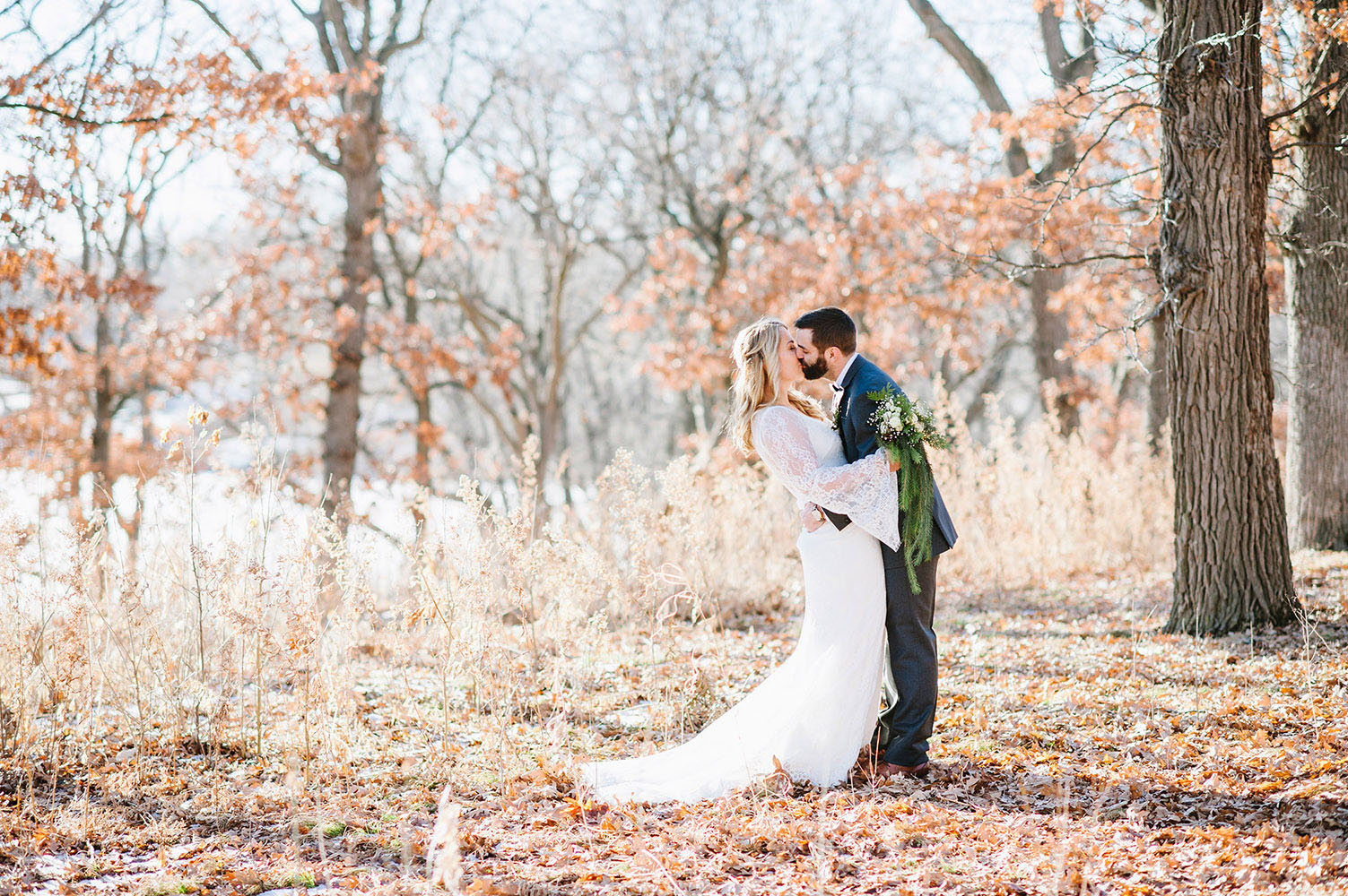 Bride in lace dress kissing groom in woods