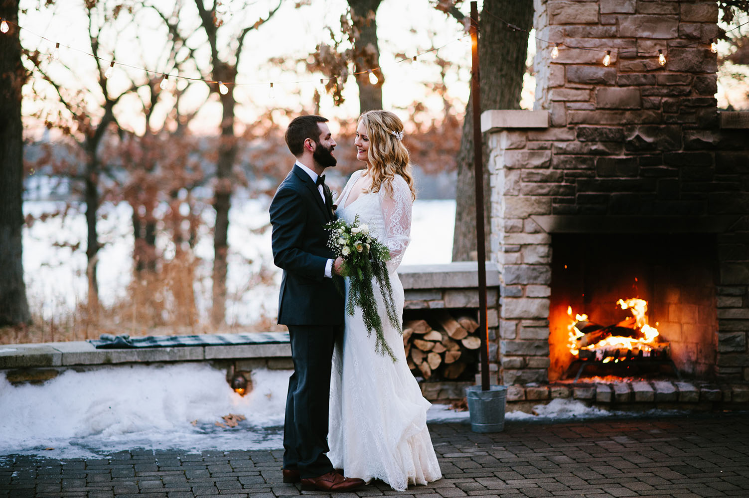 married couple by outdoor fireplace