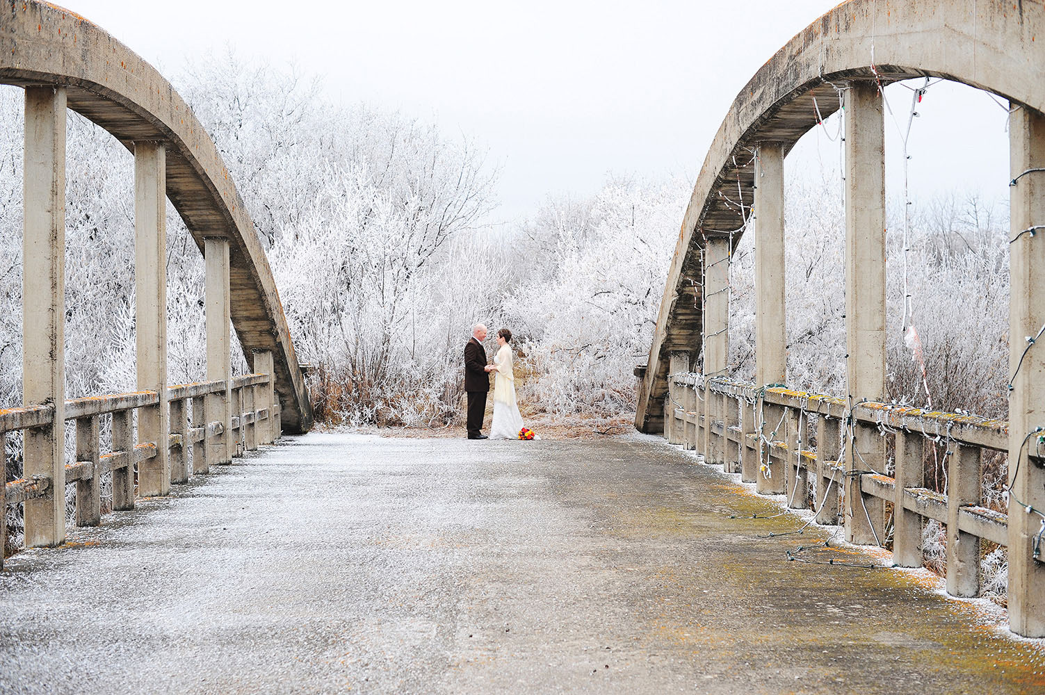 Married couple on old bridge with frost