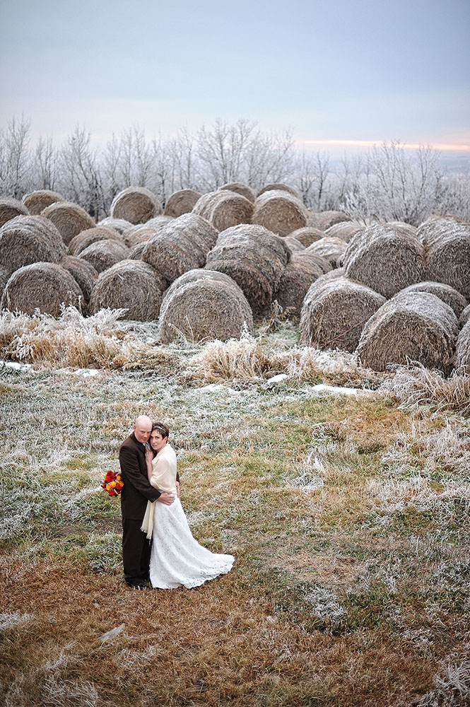 married couple in front of frosty hay bales