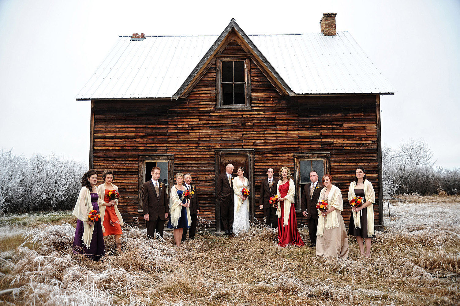Wedding party in front of old cabin