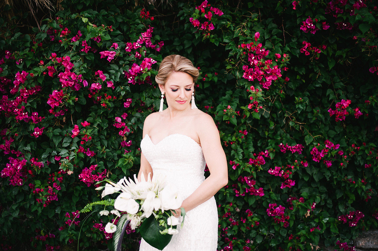 Bride in front of bougainvillea with protea bouquet a WToo dress