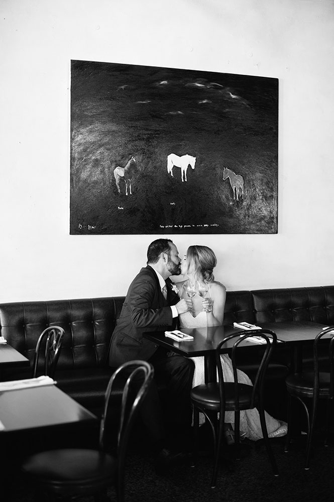 bride and groom kiss in front of horse painting at Barbette