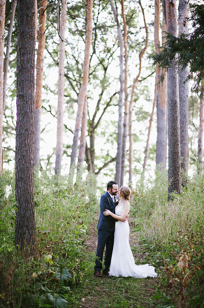 married couple kissing in tall pine trees