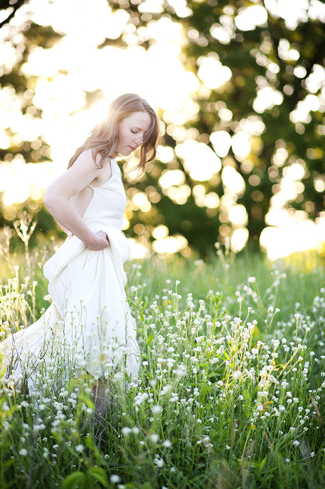 bride walking through a field at sunset