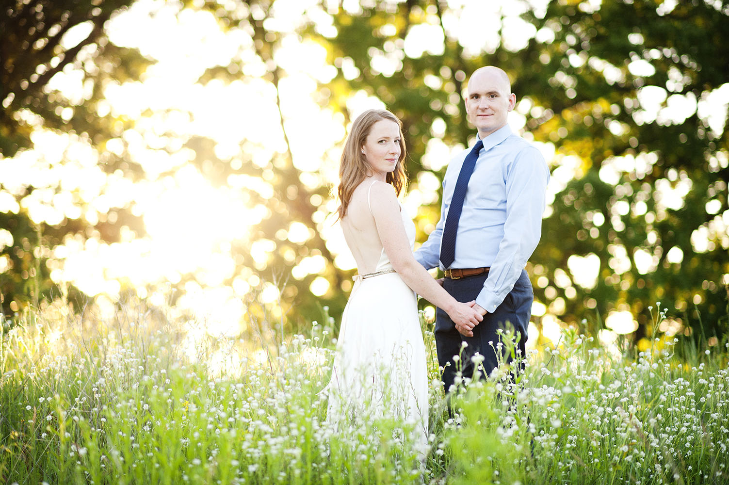 married couple in a field at sunset
