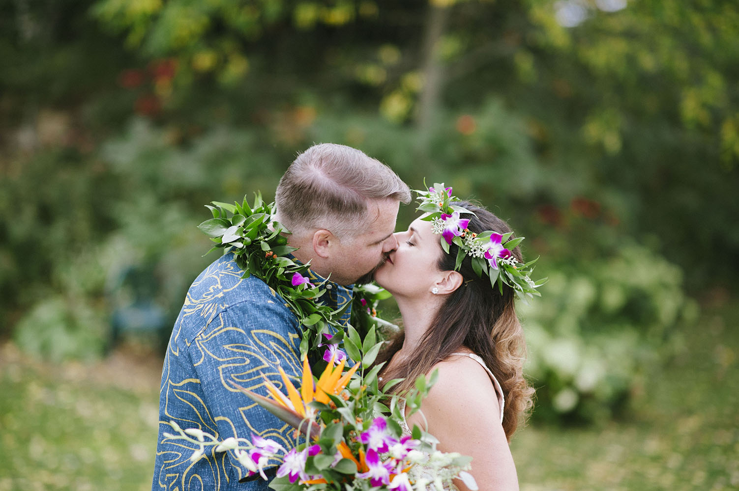 bride and groom kiss in Hawaiian attire