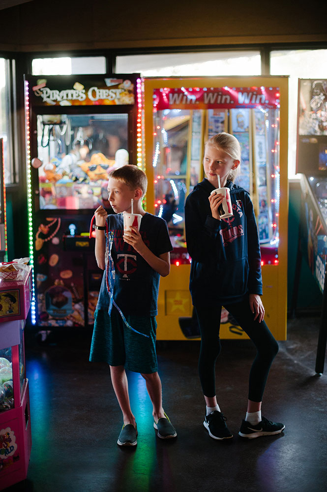 two kids at the arcade with soda