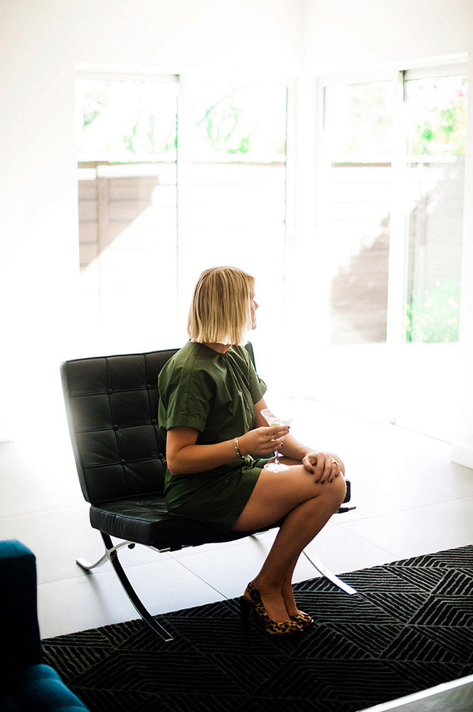 woman in green jumper with martini on Mies Van Der Rohe chair