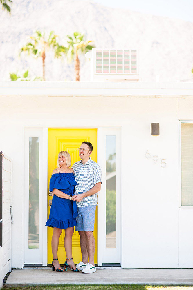 woman in blue dress with guy in blue shorts in front of yellow door of a Palm Springs house