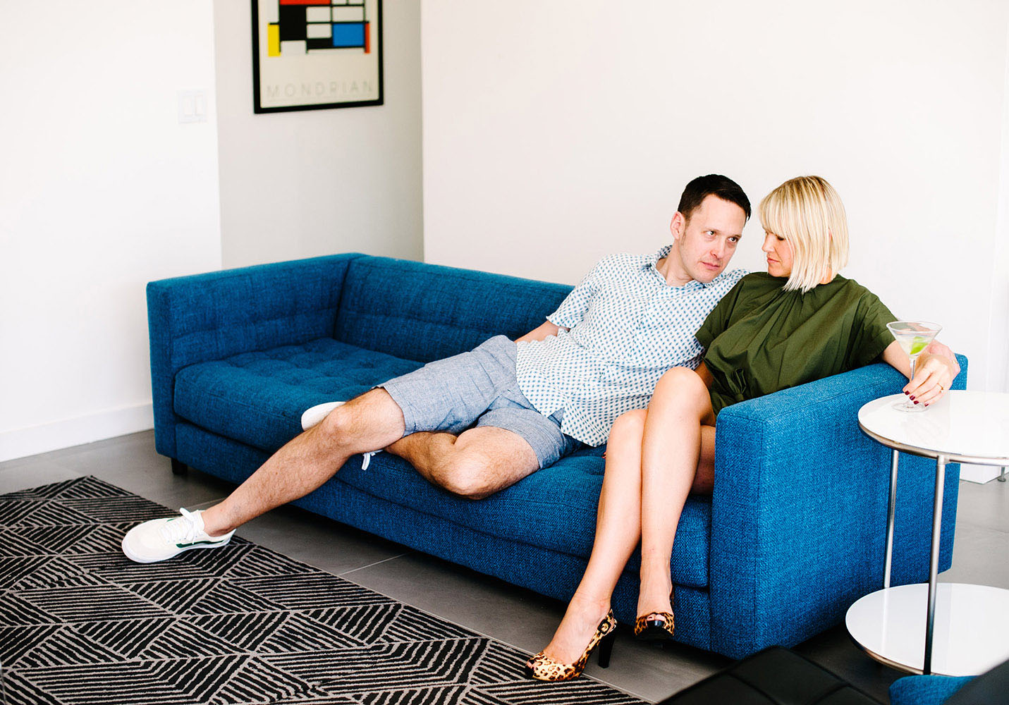 woman in green jumper with leopard print heels with martini on blue couch with guy in white shirt with blue dots and blue shorts and Mondrian print mid century modern furniture