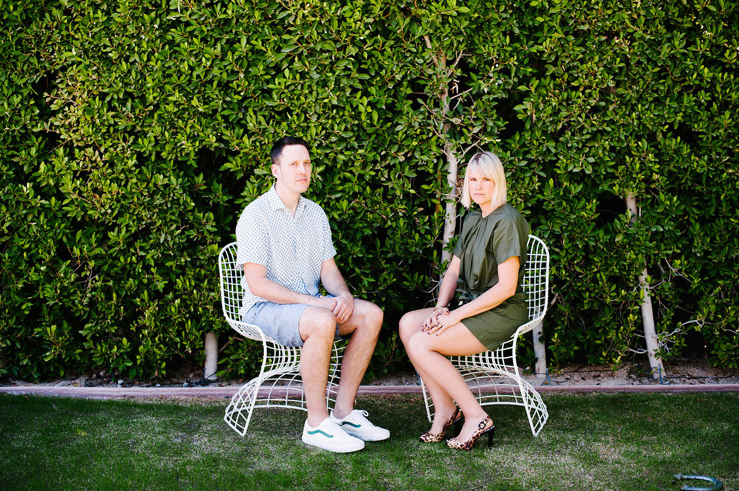 woman in green jumper with leopard print heels and guy in white shirt with blue dots in blue shorts in white wire chairs in front of green bush wall