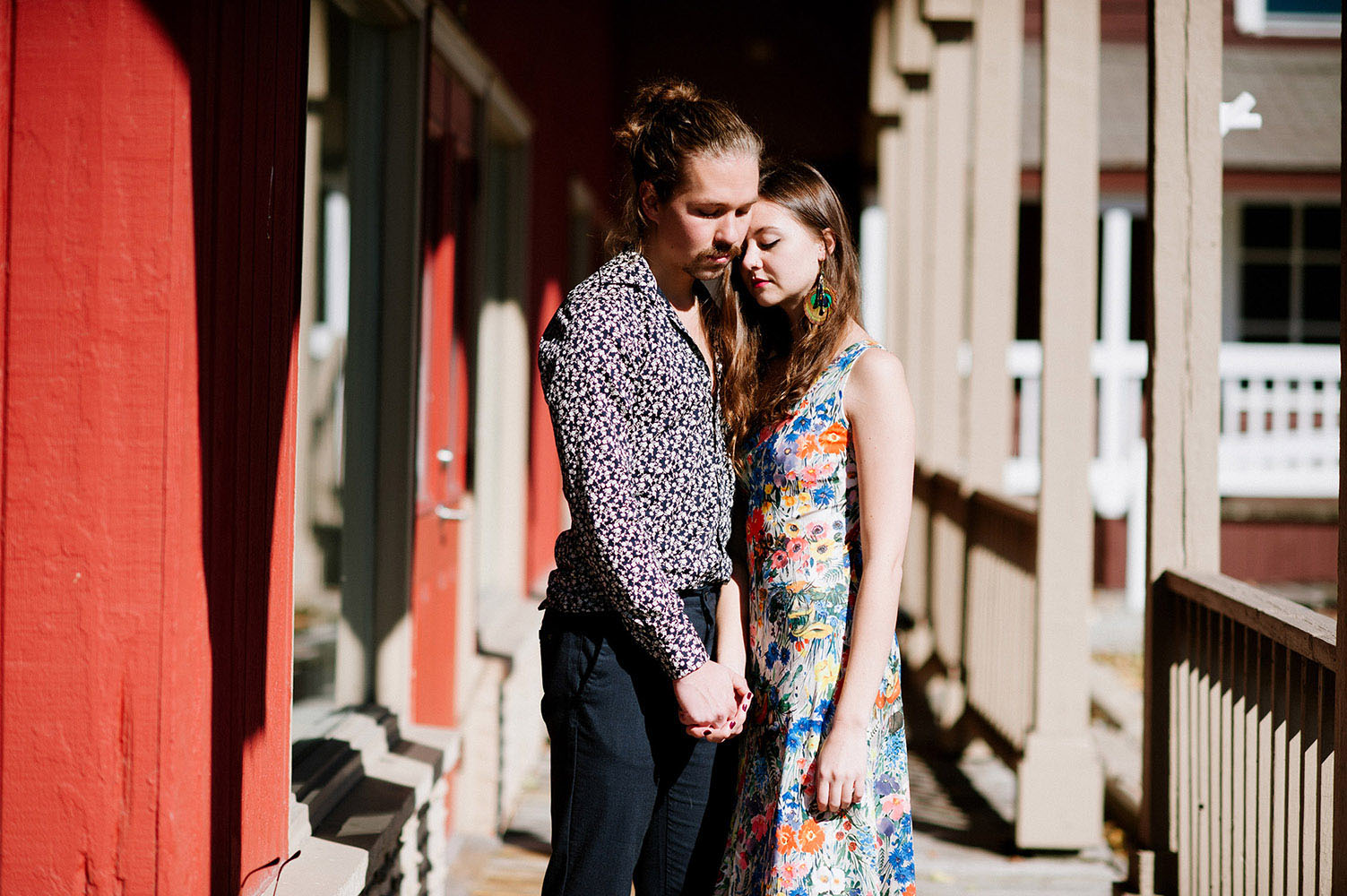 white male with facial hair and man bun with blue print shirt and female with long brown hair, peacock feahter earrings and floral print dress embracing