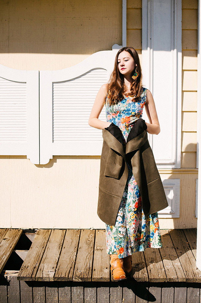 Girl with long brown hair, peacock feather earrings and long floral dress with long green coat in front of yellow western building