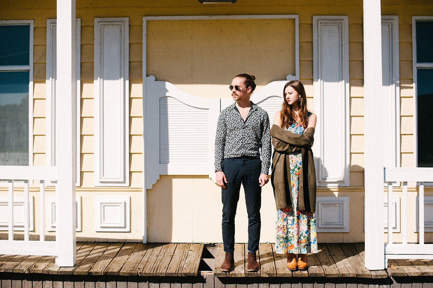 Guy with man bun, round sunglasses and blue print shirt and girl with long brown hair, long floral print dress and cowboy boots in front of yellow western style building