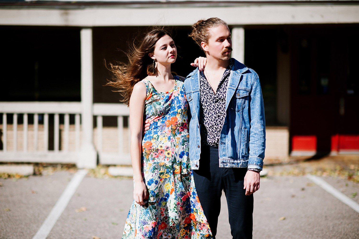 Girl with brown hair blowing in the wind, peacock feather earrings and long floral print dress and guy with man bun and jean jacket