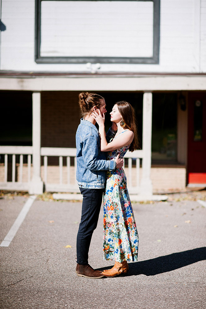 hipster guy in jean jacket girl with long floral dress in Western setting