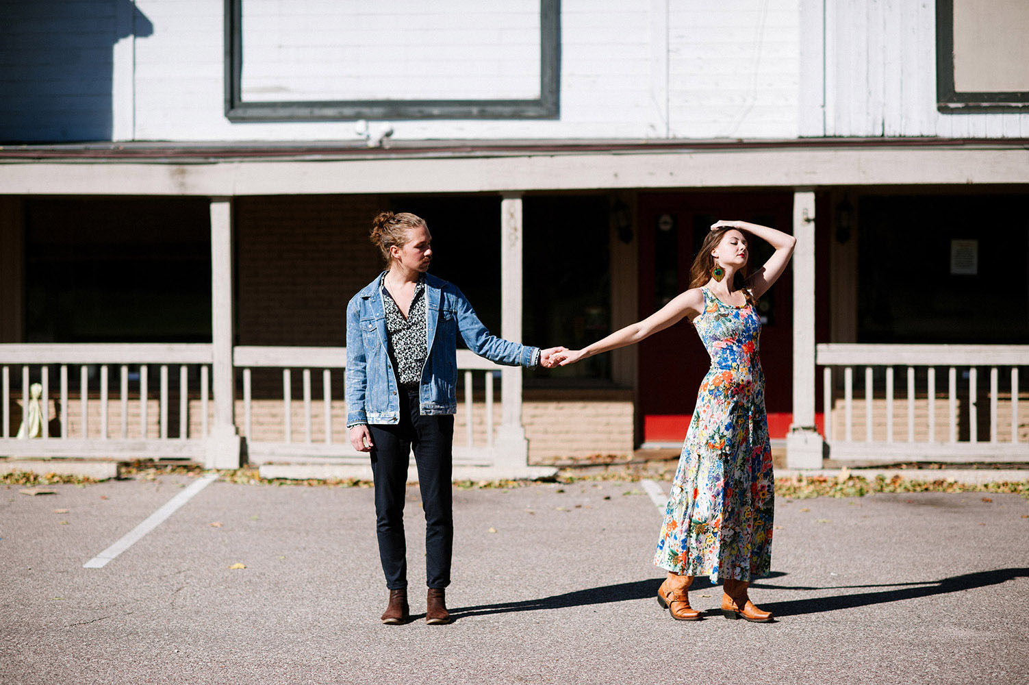male with man bun and jean jacket and woman in long floral print dress, cowboy boots and peacock feather earrings in front of old Western building
