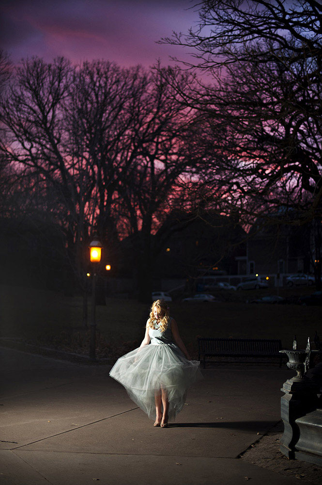 girl in pale blue tulle dress at night with pink and purple sunset