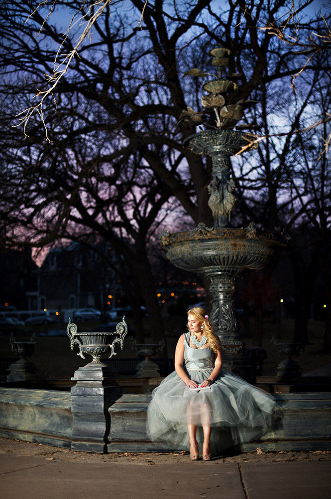 girl in pale blue tulle dress with blue flower necklace at Irvine Park fountain with blue and purple sunset