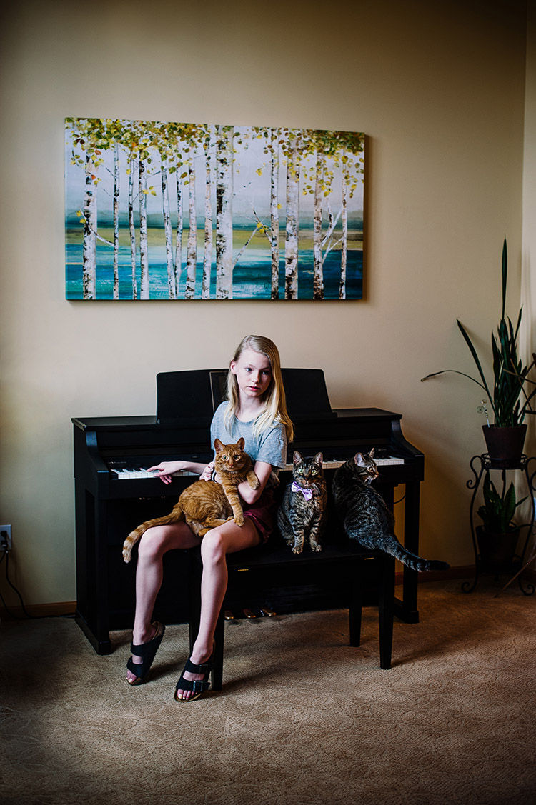 girl on a piano bench with 3 cats