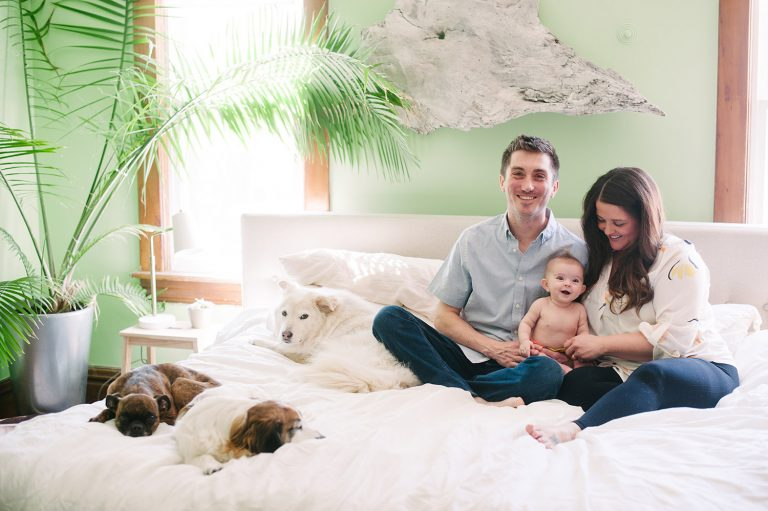 a couple on their bed with baby and dogs